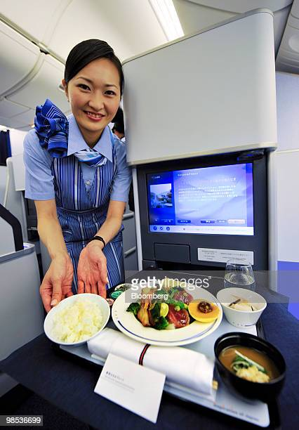 A flight attendant demonstrates the serving of a meal during the unveiling of All Nippon Airways Co's new branded service 'Inspiration of Japan'...