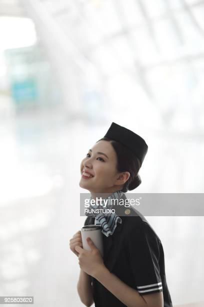 Flight attendant drinking coffee  in airport