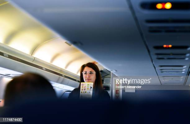 A flight attendant encourages passengers to review the safety information card in seat pockets before taking off from Denver International Airport in...