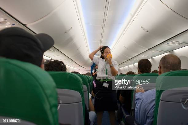 A flight attendant gives a safety demonstration showing the passengers how to use the oxygen mask on board a Transavia plane as it taxis to take off...