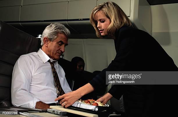 Flight Attendant Giving Man a Salad