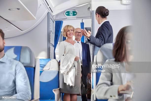 Flight attendant greeting passengers boarding airplane