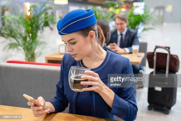Flight attendant having coffee and using her cell phone at the airport