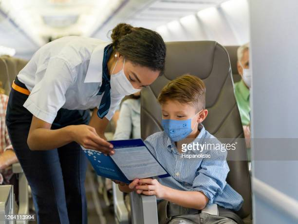 flight attendant helping a boy in an airplane and both wearing a facemask - crew stock pictures, royalty-free photos & images