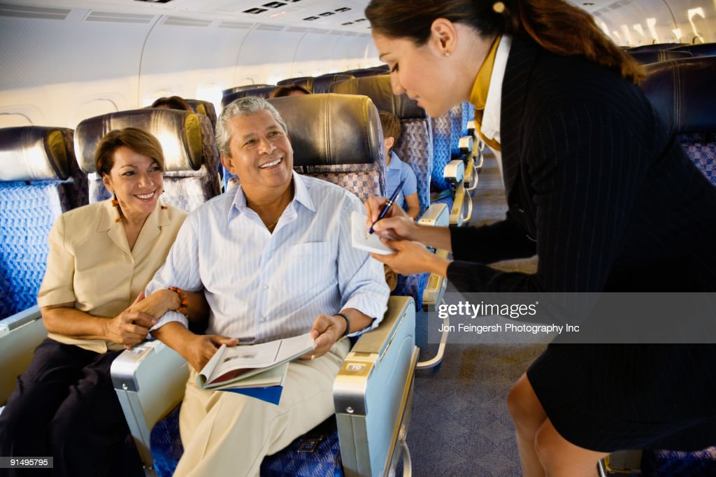 Flight attendant helping couple on airplane : Stock Photo