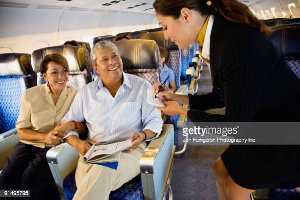 Flight attendant helping couple on airplane