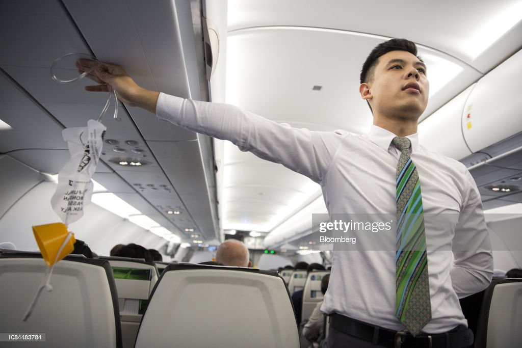 A flight attendant holds an oxygen mask during a safety