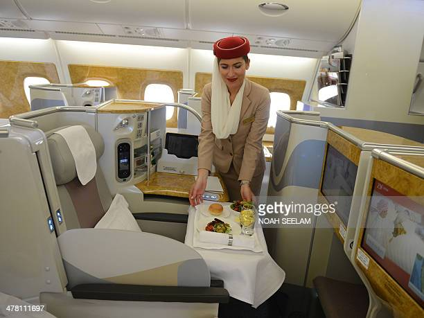 A flight attendant is pictured in the executive suite cabin of an Emirates Airbus A380 the world's largest passenger airliner during a photo call at...