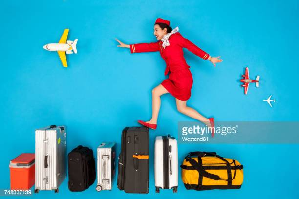Flight attendant jumping over row of luggage