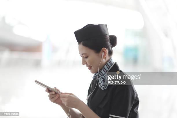 Flight attendant listening to music in airport