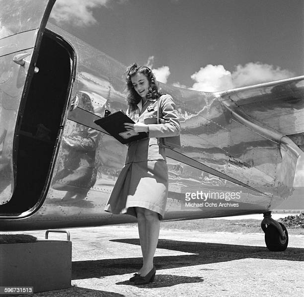A flight attendant looks over the passenger list of the British West Indian Airlines plane at the Piarco International Airport in Piarco Trinidad...