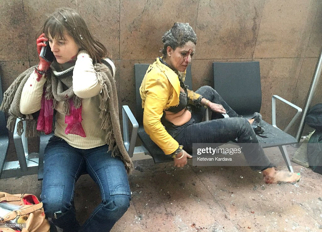 Flight attendant Nidhi Chaphekar (R) reacts in the moments following a suicide bombing at Brussels Zaventem airport on March 22, 2016 in Brussels, Belgium. Georgian journalist Ketevan Kardava, special correspondent for the Georgian Public Broadcaster, was travelling to Geneva when the attack took place, she was knocked to the floor and began to take photographs in the moments that followed. At least 31 people were killed and more than 260 injured in a twin suicide blast at Zaventem Airport and a further bomb attack at Maelbeek Metro Station. Two brothers are thought to have carried out the attacks and a manhunt is underway for a third suspect.