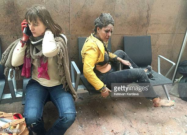 Flight attendant Nidhi Chaphekar reacts in the moments following a suicide bombing at Brussels Zaventem airport on March 22 2016 in Brussels Belgium...