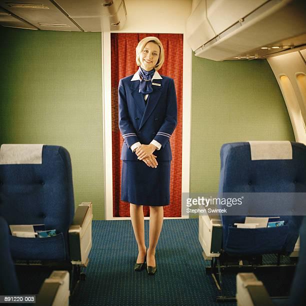 Flight attendant on commercial airliner, smiling