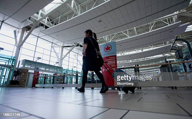 Flight attendant passes in front of the Air Canada check-in counters at Vancouver International Airport in Richmond, British Columbia, Canada, on...