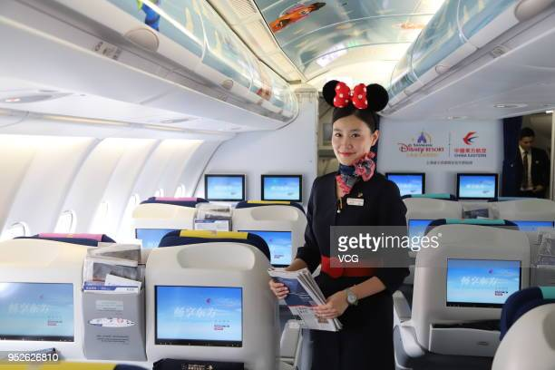 A flight attendant provides service at a Disney Pixar Toy Storythemed aircraft launched by China Eastern Airlines before its maiden flight from...