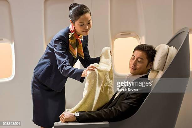 Flight attendant putting blanket on sleeping man