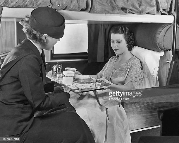 Flight attendant serves coffee and sandwiches to a passenger on board an American Airlines flight, circa 1935.