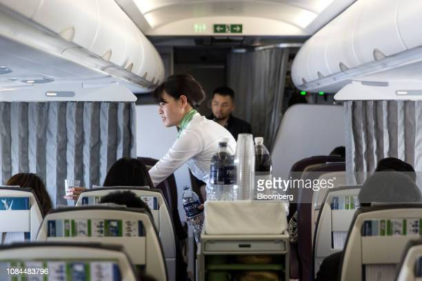 A flight attendant serves drinks to passengers in the economy class cabin on board an Airbus SE A321 Neo aircraft operated by FLC Group JSC's Bamboo...