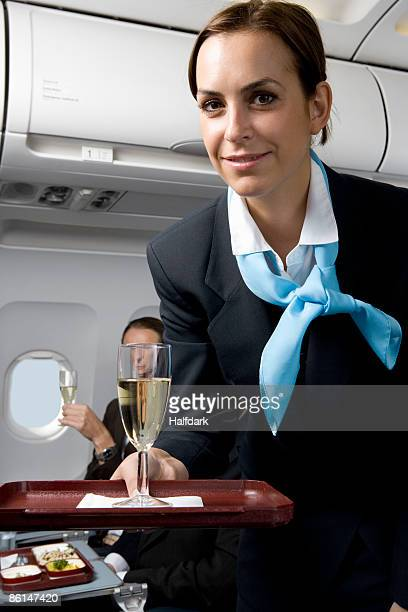 A flight attendant serving champagne