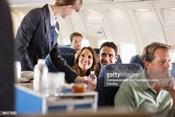 flight attendant serving customers on an airplane - porzione di cibo foto e immagini stock