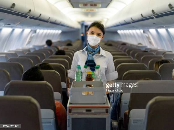 flight attendant serving drinks in an airplane wearing a facemask - crew stock pictures, royalty-free photos & images