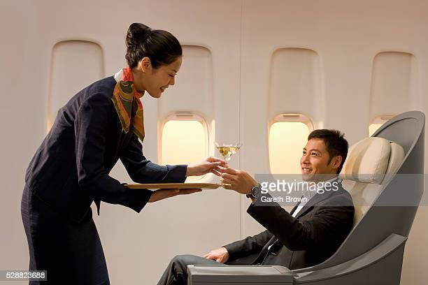 Flight attendant serving man martini