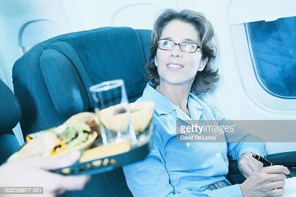Flight attendant serving meal to female passenger