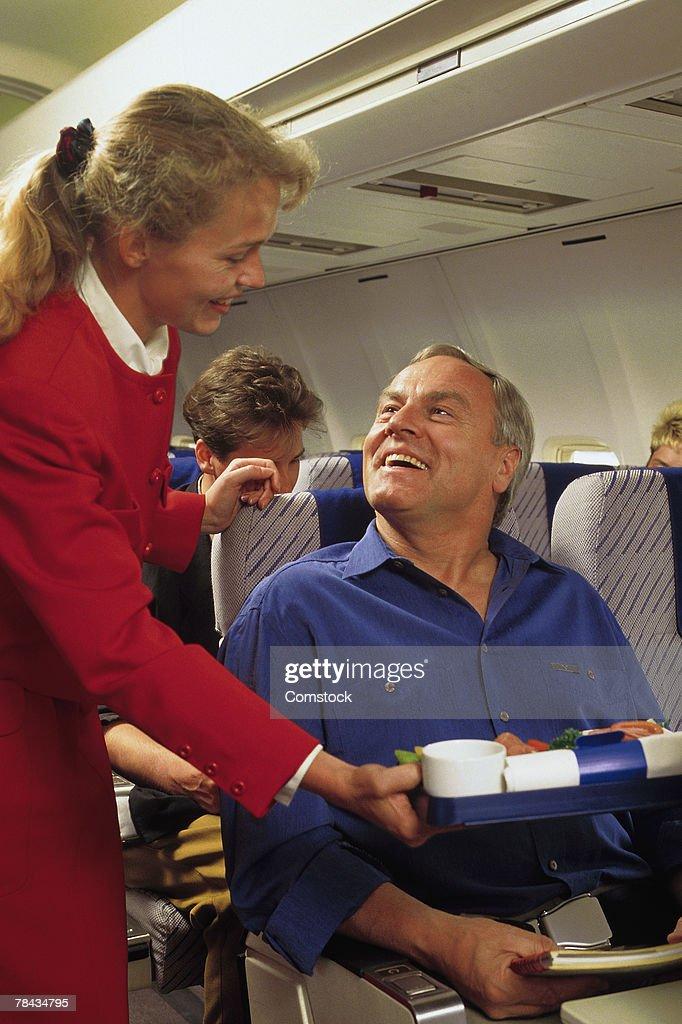 Flight attendant serving passenger on airplane : Stockfoto