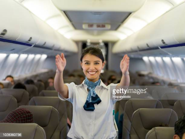 flight attendant showing the emergency exit in an airplane - crew stock pictures, royalty-free photos & images