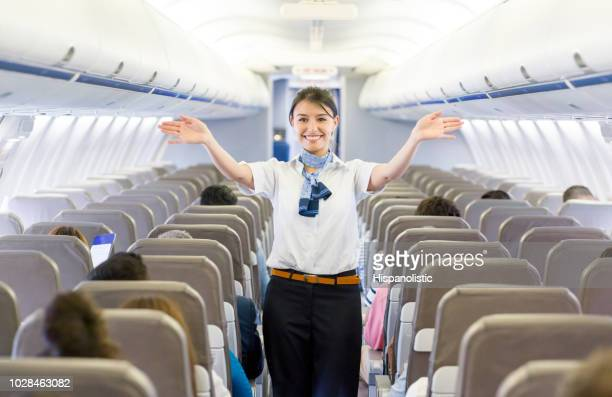 Flight attendant showing the emergency exit in an airplane