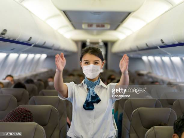 flight attendant showing the emergency exit in an airplane wearing a facemask - crew stock pictures, royalty-free photos & images
