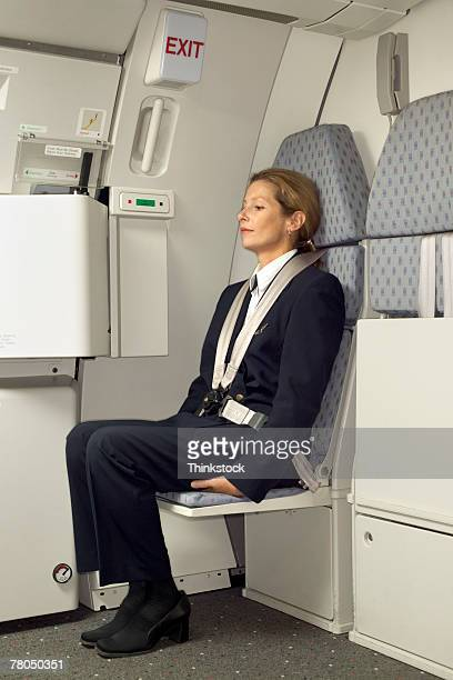 flight attendant sitting in a jump seat - strap stock photos and pictures