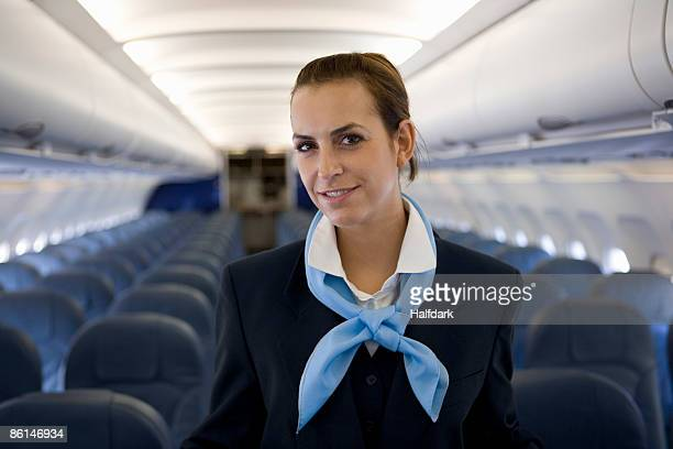 A flight attendant standing in the cabin of a plane