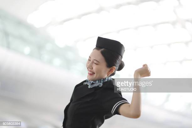 Flight attendant  standing with arms raised in airport