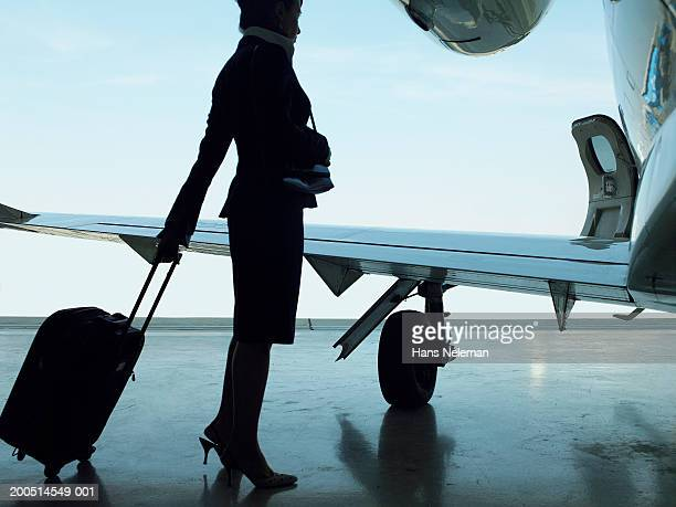 Flight attendant standing with suitcase near airplane, side view