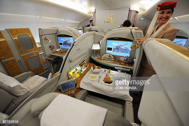 A flight attendant stands next to first class seats aboard an Emirates Airlines A380 on August 1 2008 Emirates becomes the first commercial Airbus...