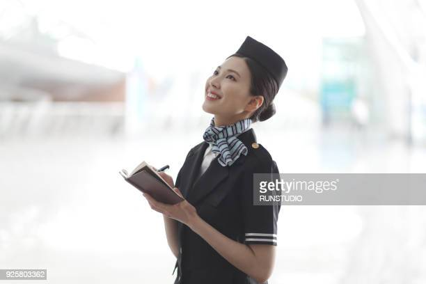 Flight attendant taking note in airport