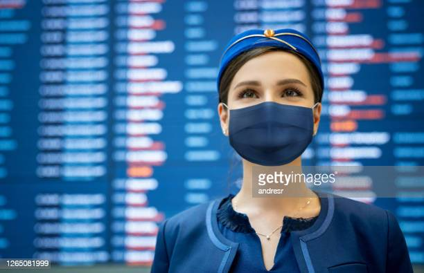 flight attendant wearing a facemask at the airport - crew stock pictures, royalty-free photos & images