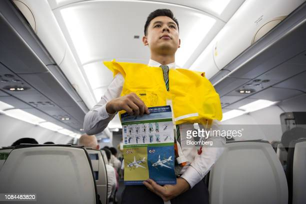 A flight attendant wearing an inflatable life vest holds an instructions card during a safety demonstration on board an Airbus SE A321 Neo aircraft...