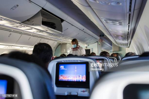 Flight attendant wearing personal protective equipment walks through the cabin on a flight from Vancouver International Airport to Toronto...