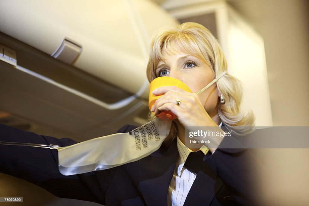 Flight attendant with an oxygen mask : Stock Photo
