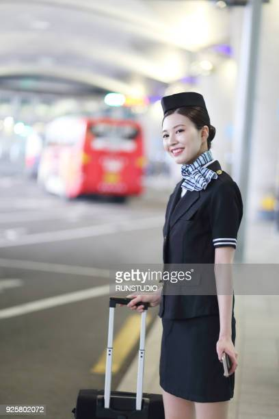 Flight attendant with suitcase waiting for bus