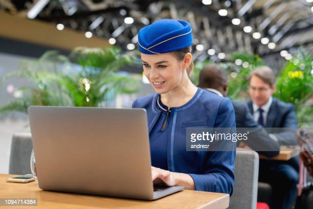 Flight attendant working online at the airport waiting for her flight