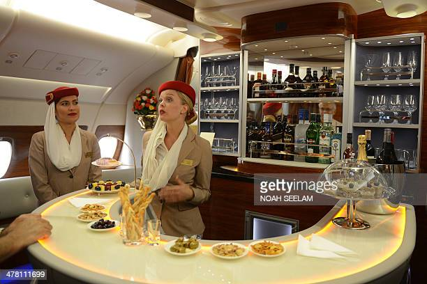Flight attendants are pictured at the bar of the executive suite cabin of an Emirates Airbus A380 the world's largest passenger airliner during a...
