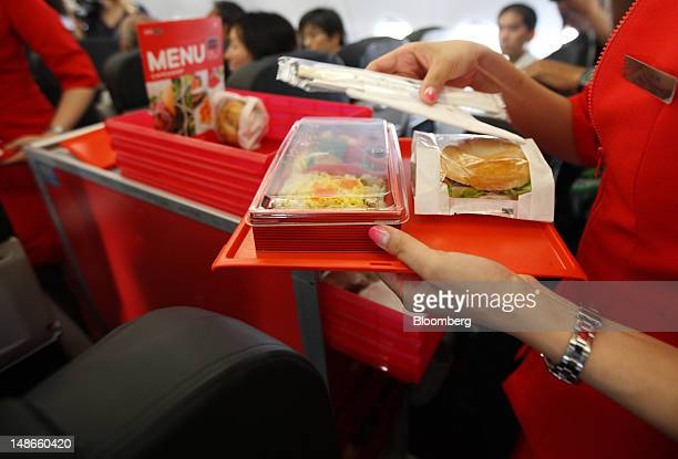 Flight attendants deliver meals inside an AirAsia Japan Co Airbus SAS A320 aircraft during the unveiling of the plane's new livery at Narita Airport...