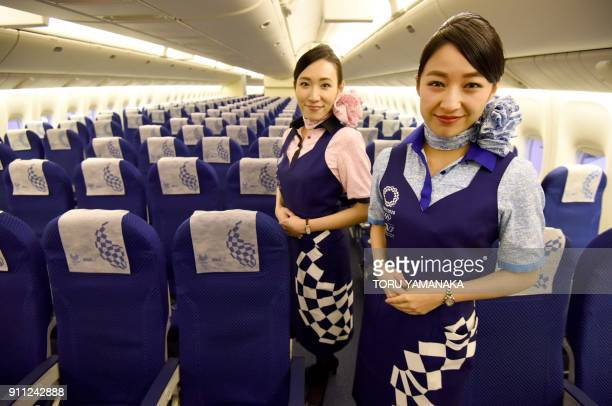 Flight attendants for Japanese airline All Nippon Airways pose to display aprons and headrest covers printed with emblems of the 2020 Tokyo Olympic...