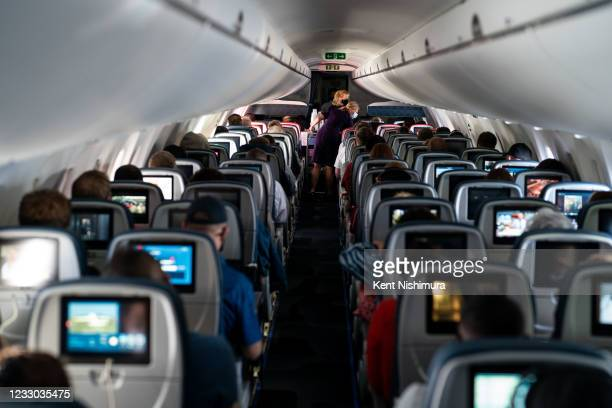 Flight attendants hand out refreshments to a packed Delta Airlines flight traveling from Ronald Regan National Airport to MinneapolisSaint Paul...