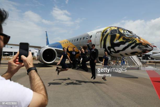 Flight attendants pose for a photograph in front of a prototype of the Embraer SA E190 E2 passenger aircraft on display during a media preview day at...