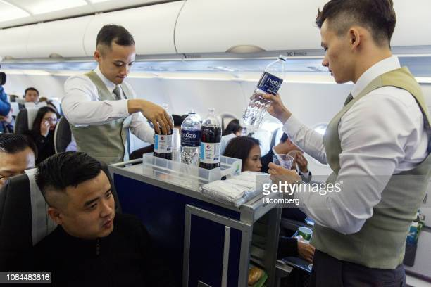 Flight attendants serve drinks to passengers in the economy class cabin on board an Airbus SE A321 Neo aircraft operated by FLC Group JSC's Bamboo...